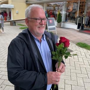 Wolfgang Hellmich mit roten Rosen in der Hand